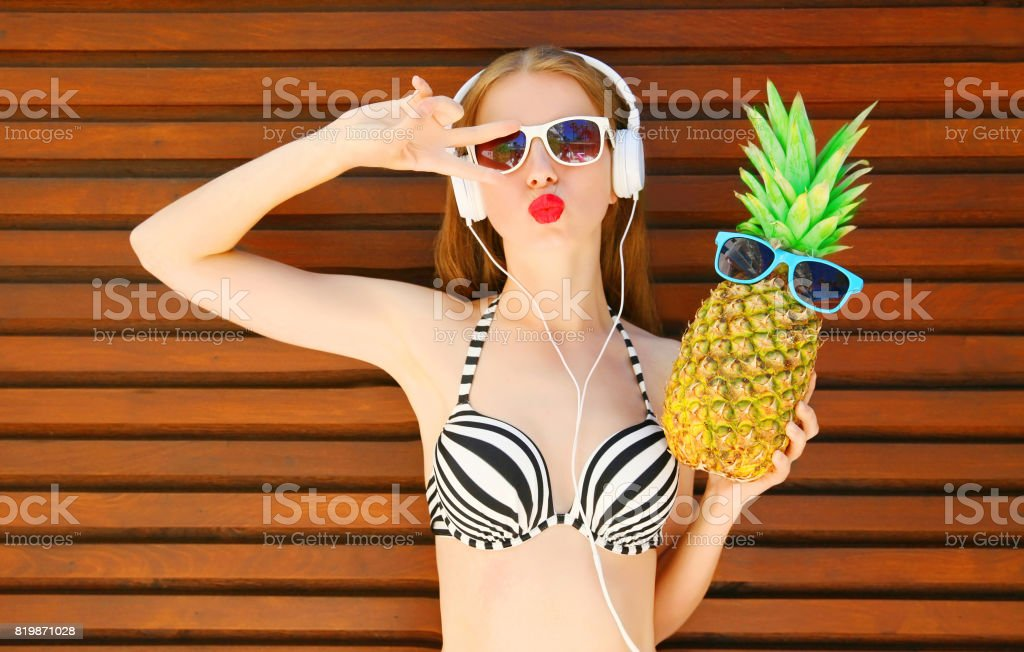 Pretty Young Woman With Funny Pineapple Listens To Music In
