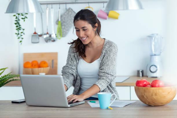 Hübsche junge Frau arbeiten mit Laptop und Dokumente in der Küche zu Hause. – Foto
