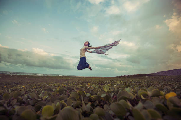 Pretty young women jumping in breezy wind Pretty young women jumping in breezy wind on meadow near beach girl power stock pictures, royalty-free photos & images