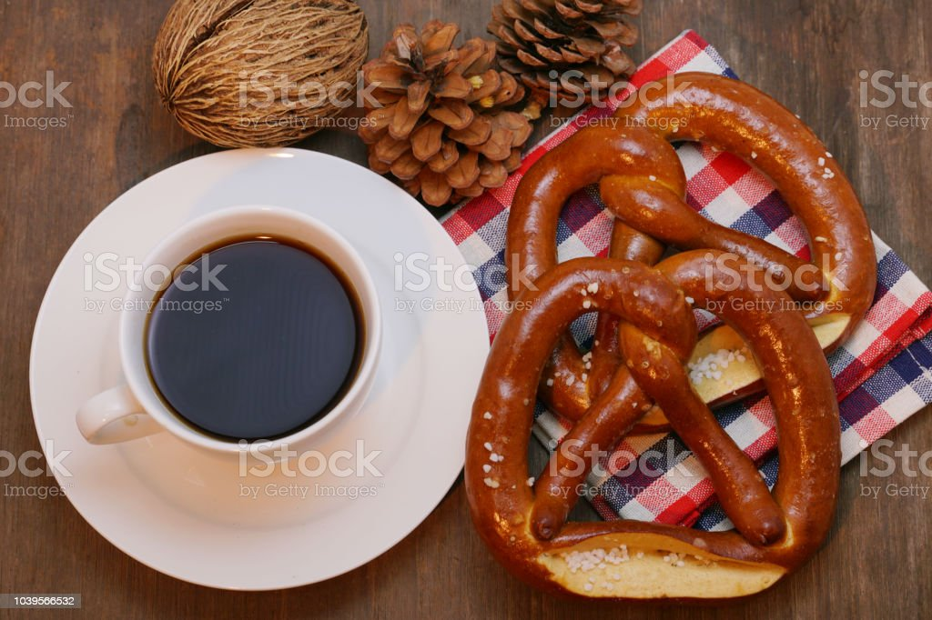 Pretzel and pine cone and checker cloth with coffee cup on wood table. stock photo