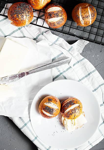 pretzel buns with poppy seeds and butter - laugenstangen stock-fotos und bilder