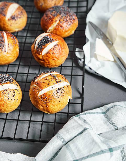 pretzel buns with poppy seeds - laugenstangen stock-fotos und bilder