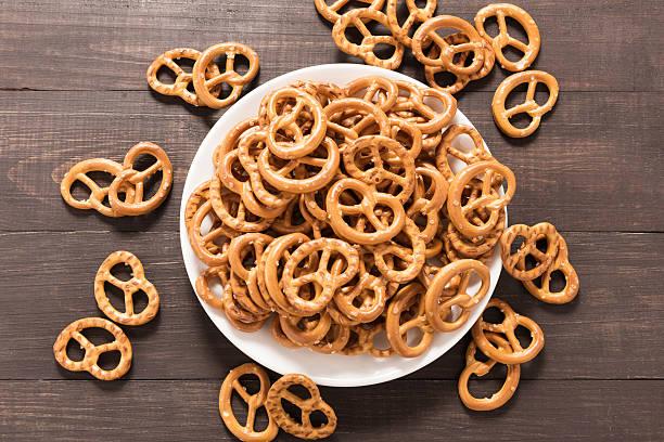 pretzel in white dish on the wooden background - 椒鹽蝴蝶圈 個照片及圖片檔