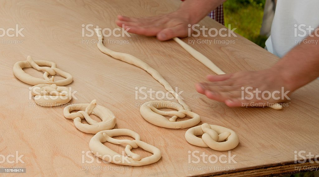 Pretzel making hands roll raw dough wooden table close up royalty-free stock photo