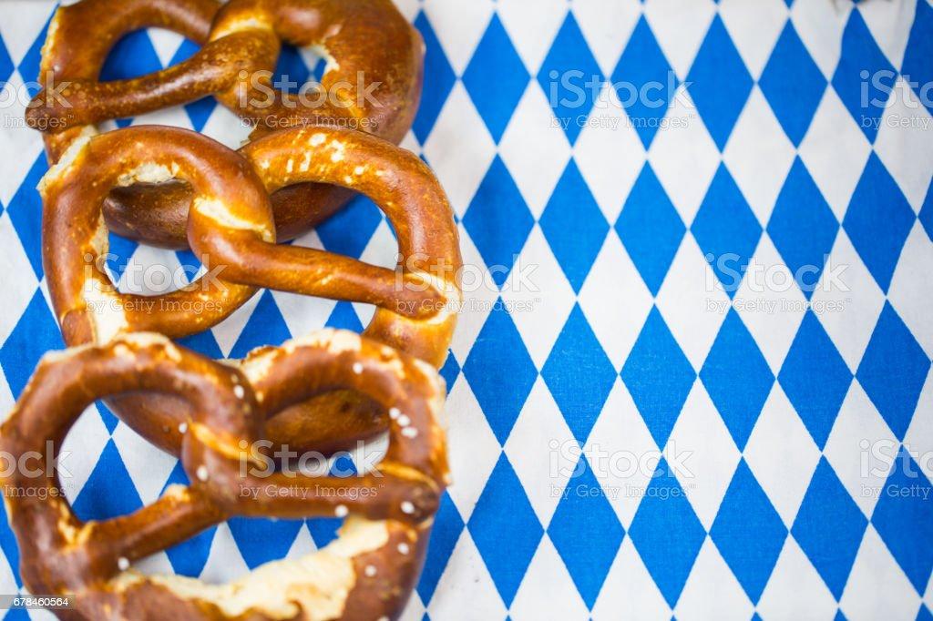 Pretzel on white / blue background. Rhombuses, Bavarian colors royalty-free stock photo