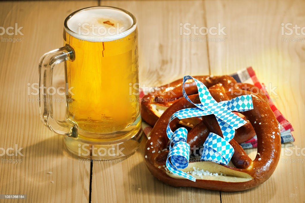 Pretzel with glass of beer on wood table for oktoberfest. stock photo
