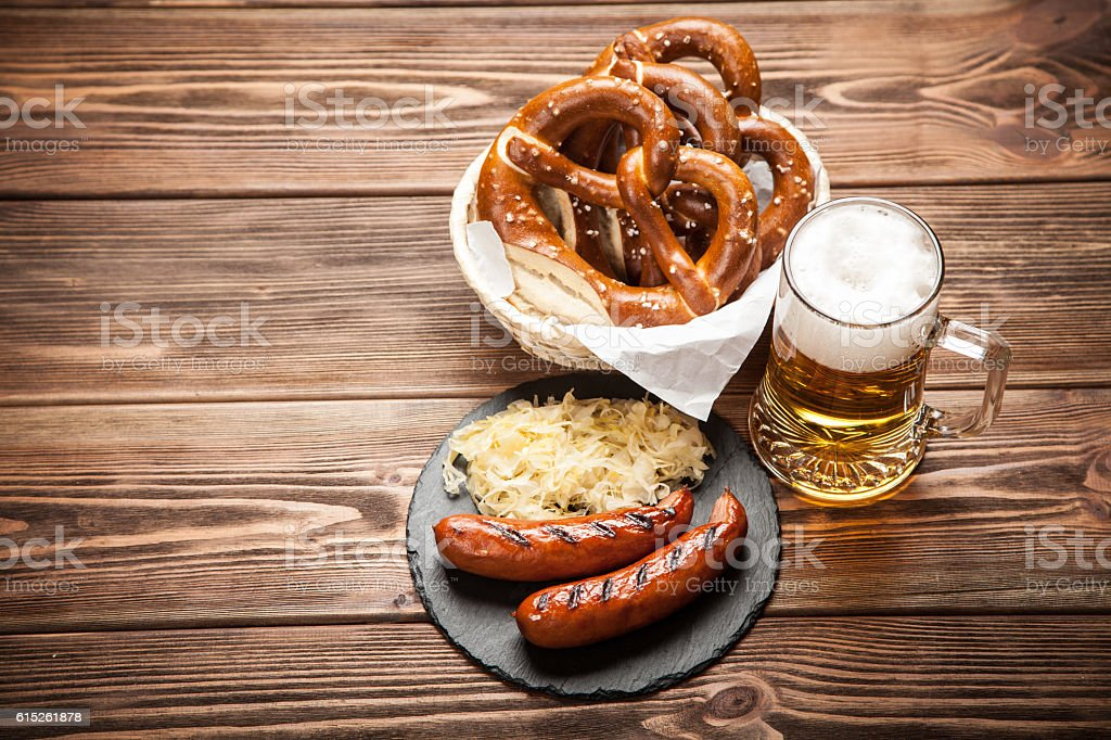 Pretzels, bratwurst and sauerkraut on wooden table stock photo