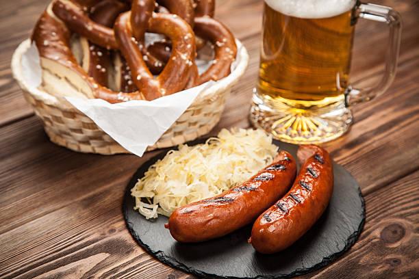 pretzels, bratwurst and sauerkraut on wooden table - bratwurst mit sauerkraut stock-fotos und bilder