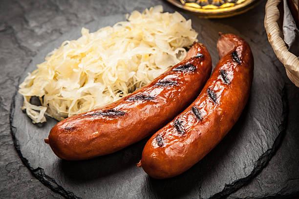 pretzels, bratwurst and sauerkraut - bratwurst mit sauerkraut stock-fotos und bilder