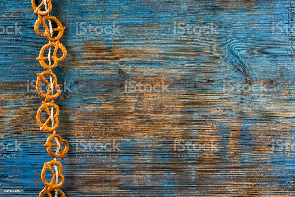 Pretzels hanging on a rope on rustic wooden background stock photo
