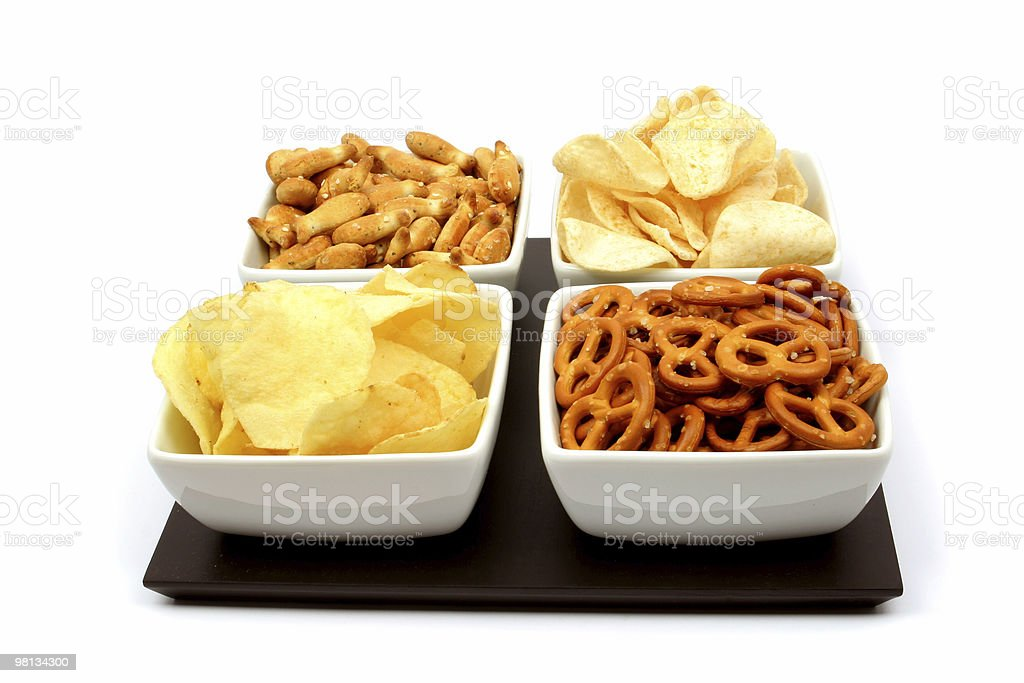 Pretzels, nuts and potato chips in four white bowls royalty-free stock photo