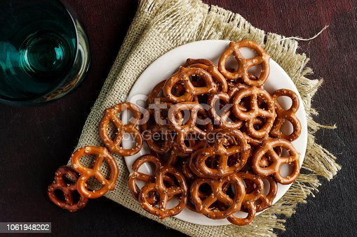 Macro photograph of pretzels on white plate on dark red black background