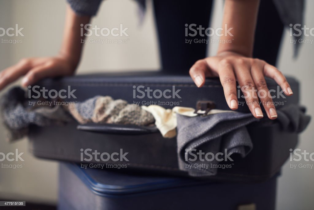 Pre-vacation stress A woman trying to close an over-full suitcase Adult Stock Photo