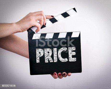 istock Price. Female hands holding movie clapper 820321618