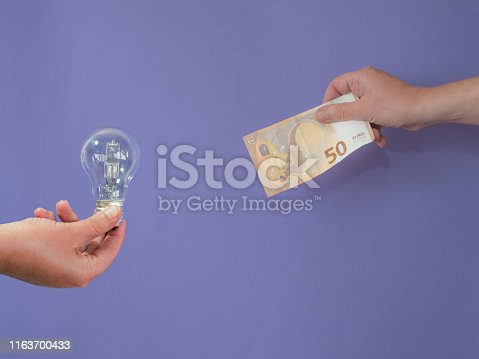 Hand with a lightbulb and another with a banknote of fifty euros on purple bankground with copy space