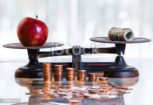 dollars and apple on the antique scales, Piles of coins at front of scales.