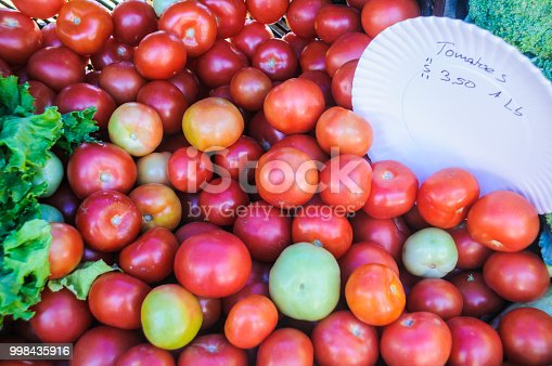 Tomatoes for sale at a Cape Cod farmers market with their price displayed.
