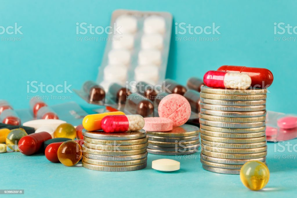 Prices of medicines - concept of medical business. Pills and coins on...