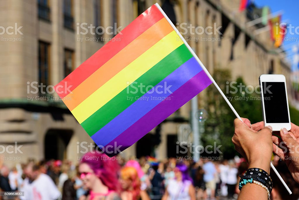 Pride flag and spectator taking pictures with mobile phone stock photo
