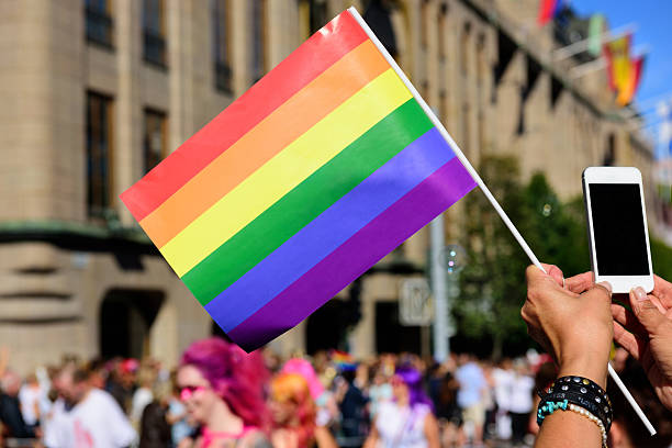 pride flag and spectator taking pictures with mobile phone - transsexual stock photos and pictures