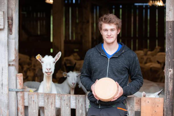 Stolz Jungbauer hält eine Ziege ganze Käse runde – Foto