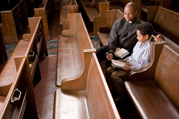 Priest and Boy in Church Pew Reading Bible stock photo