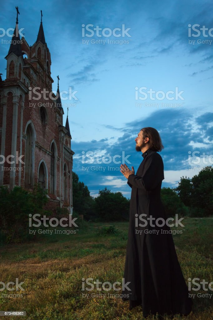 Priest during evening prayer near an old church in the evening stock photo