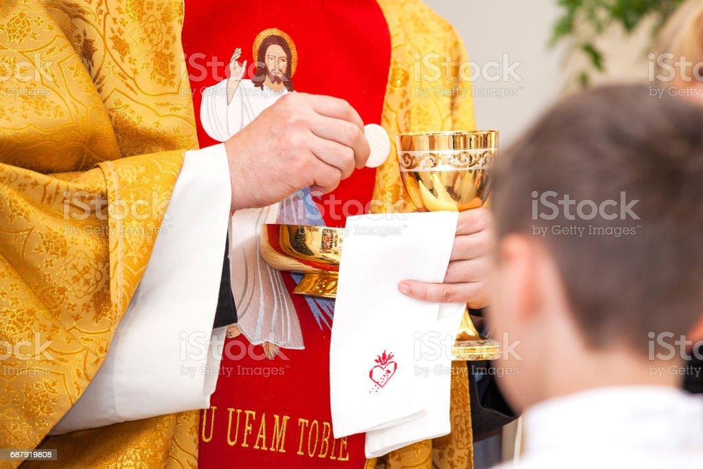 Prêtre donne la première communion. Symbole du corps et du sang du Christ. - Photo
