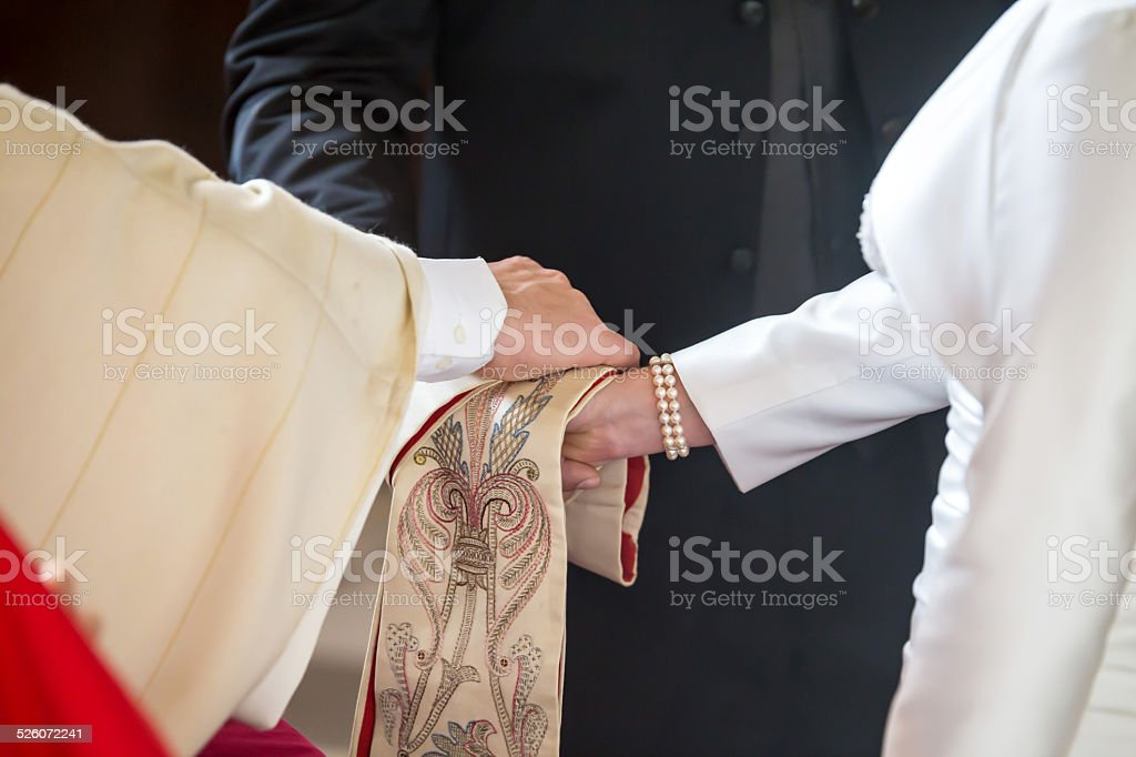 Priest giving blessing to a couple at a wedding ceremony stock photo