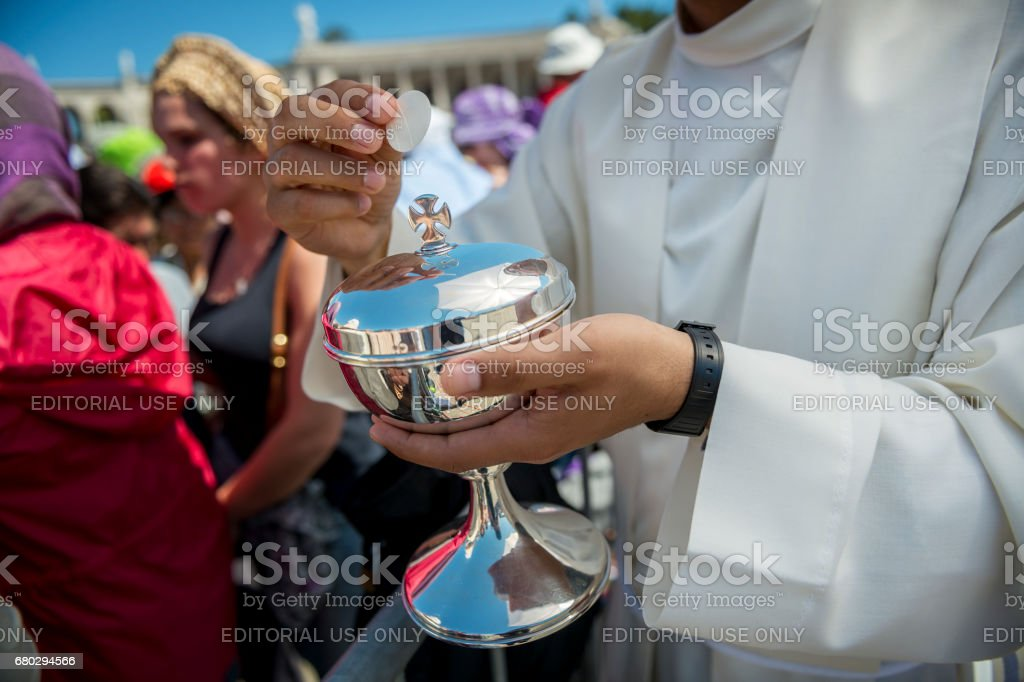 Priest holding a ciborium with sacramental bread at the Sanctuary of Fatima during the celebrations of the apparition of the Virgin Mary in Fatima, Portugal. stock photo