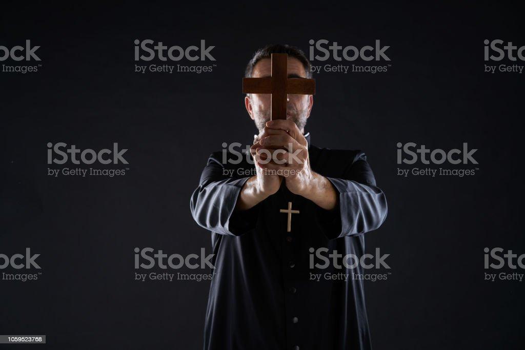 Priest holding cross of wood praying stock photo