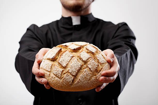 Priester hält Brotlaib – Foto