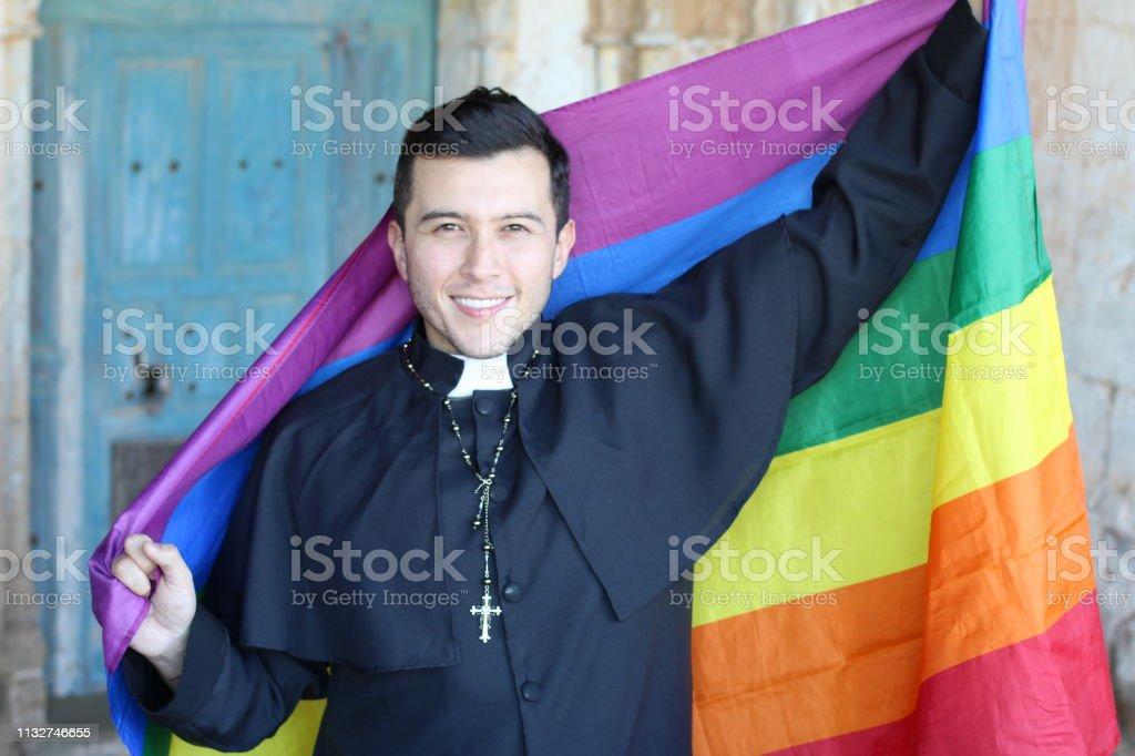 Priest que prende a bandeira do arco-íris - foto de acervo