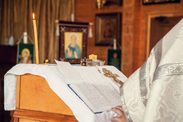 ein priester hält ein buch zum lesen von gebeten während des taufesus in der orthodoxen kirche - achtsamkeit persönlichkeitseigenschaft stock-fotos und bilder