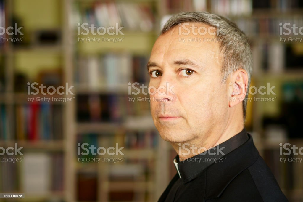 Priest in his library stock photo