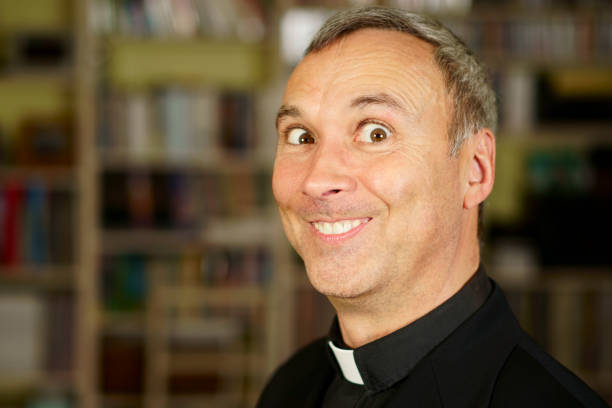 Priest in his library A good looking crazy catholic priest is into his library. He has a foolish look. approbation stock pictures, royalty-free photos & images