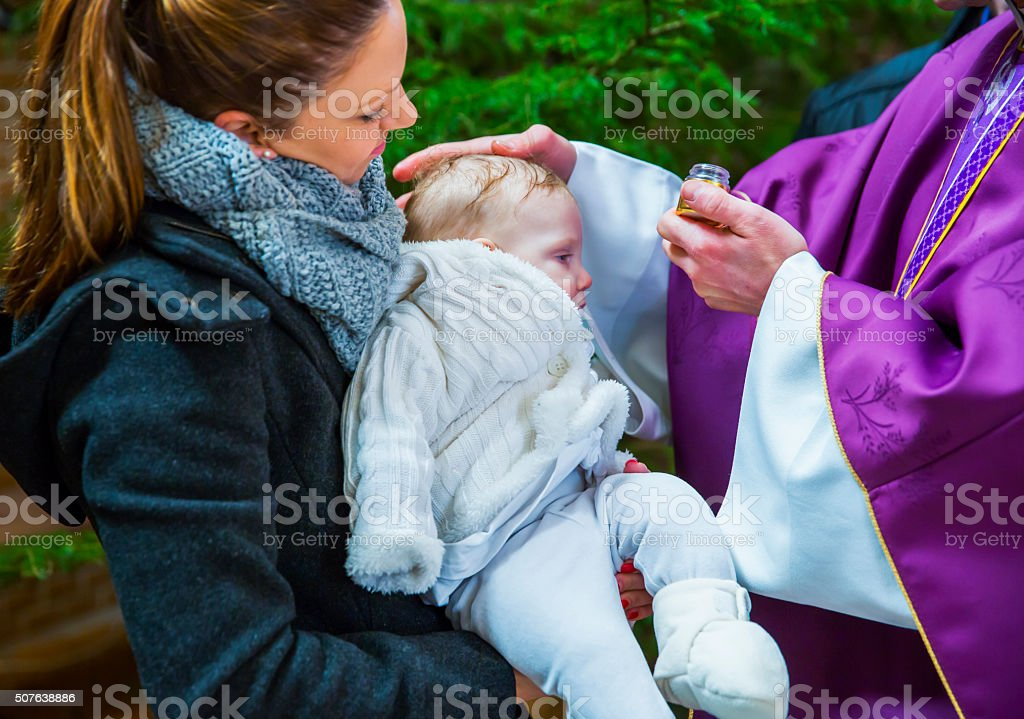 Priest is baptizing little baby girl in a church stock photo
