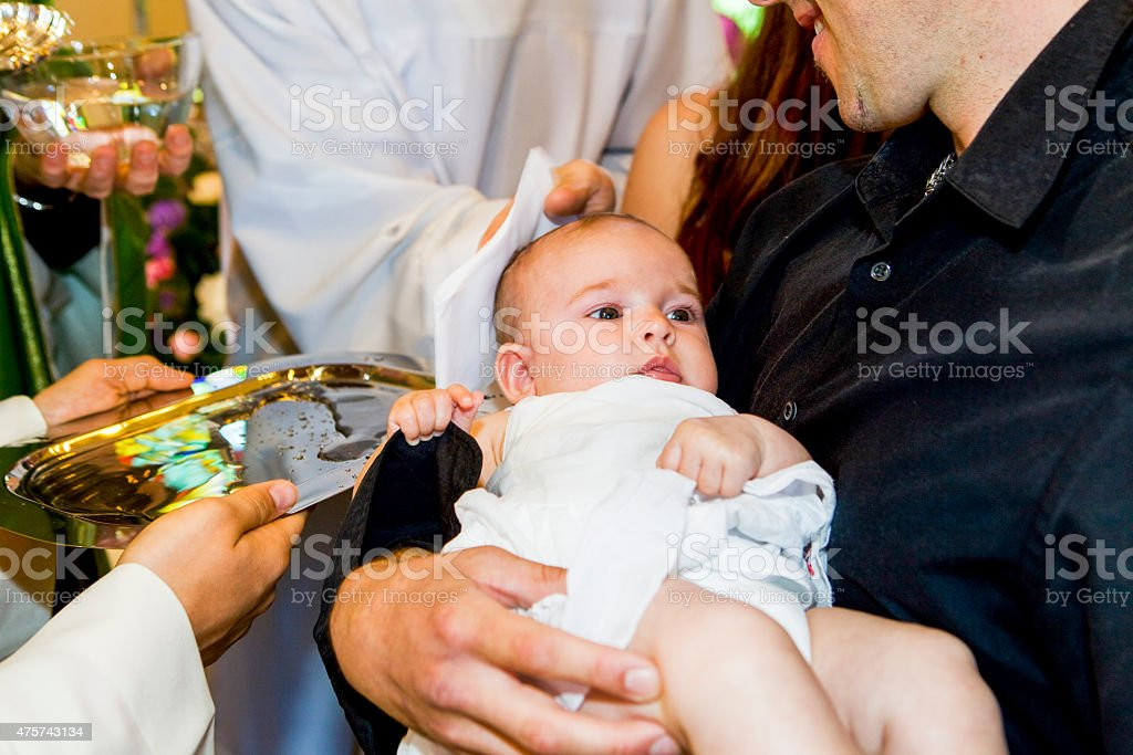 Priest is baptizing little baby in a church. stock photo
