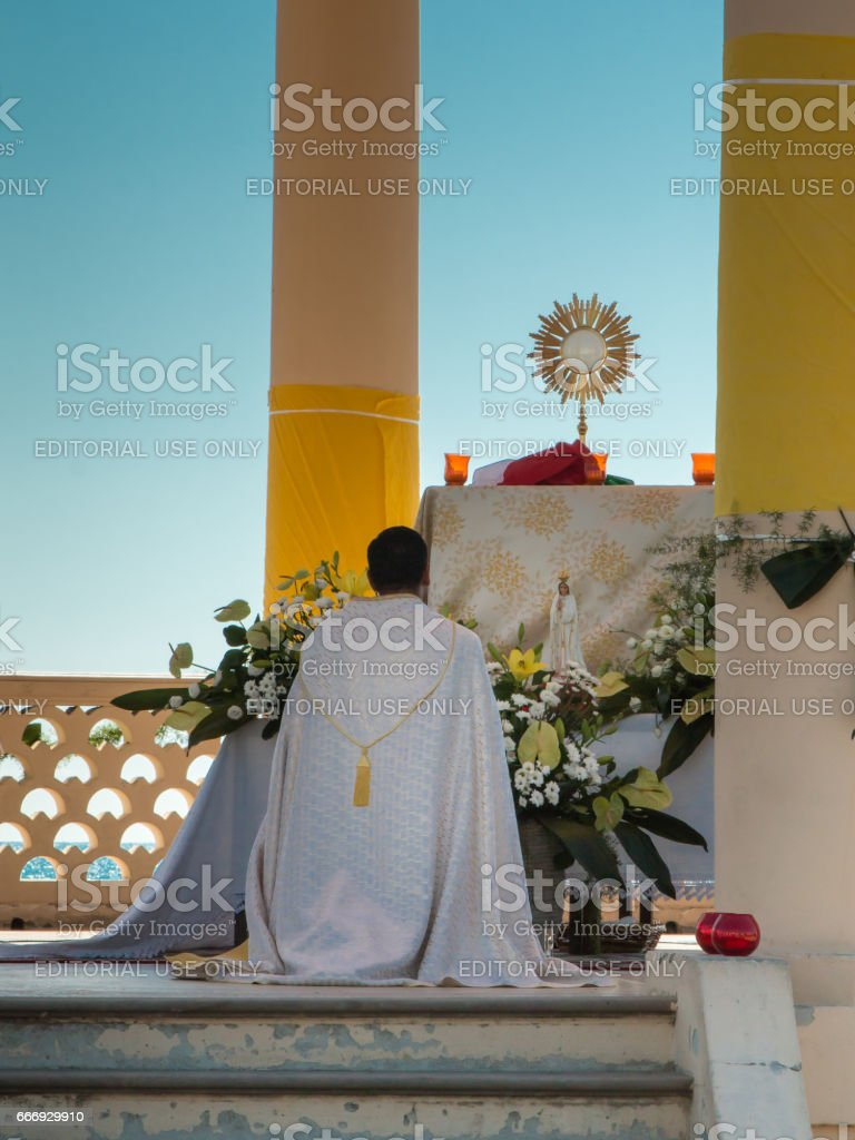 Priest Kneel Down in front of an Altar with Golden Ostensory: Outdoor Church stock photo