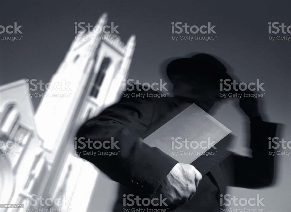 Priest Man Carrying Book and Leaving Church royalty-free stock photo