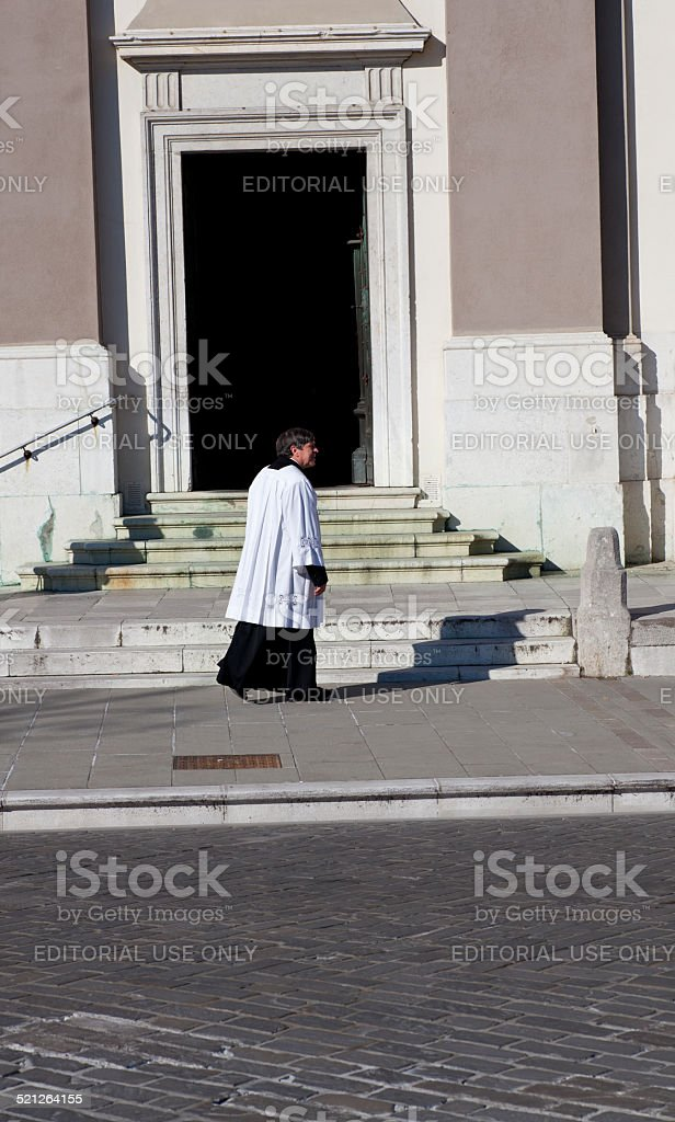 Priest next to the church stock photo