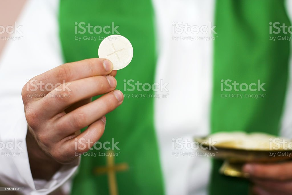 Priest of communion in the hand stock photo