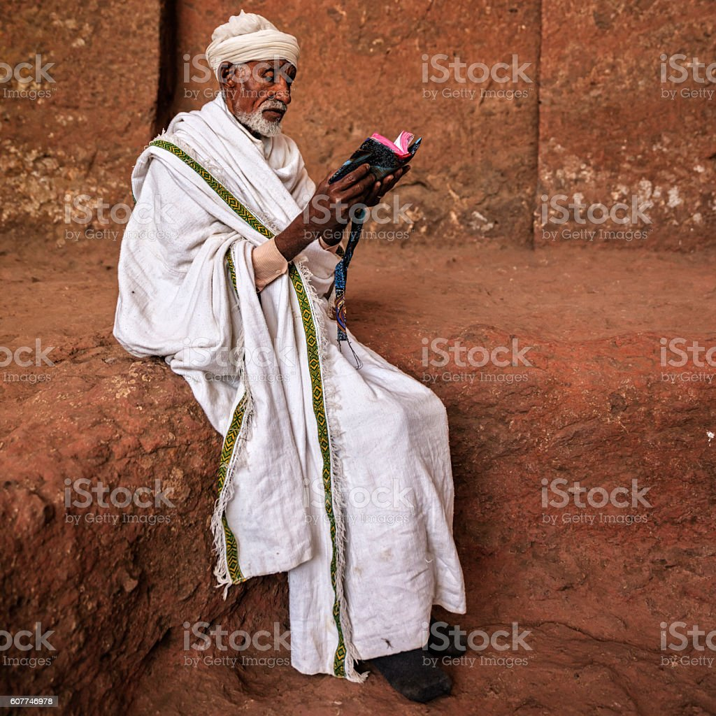 Priest of rock-hewn church reading holy book, Lalibela stock photo