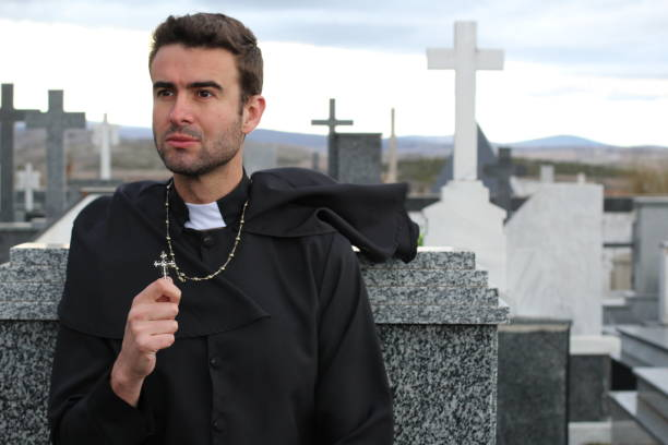 Priest performing an exorcism in a cemetery stock photo