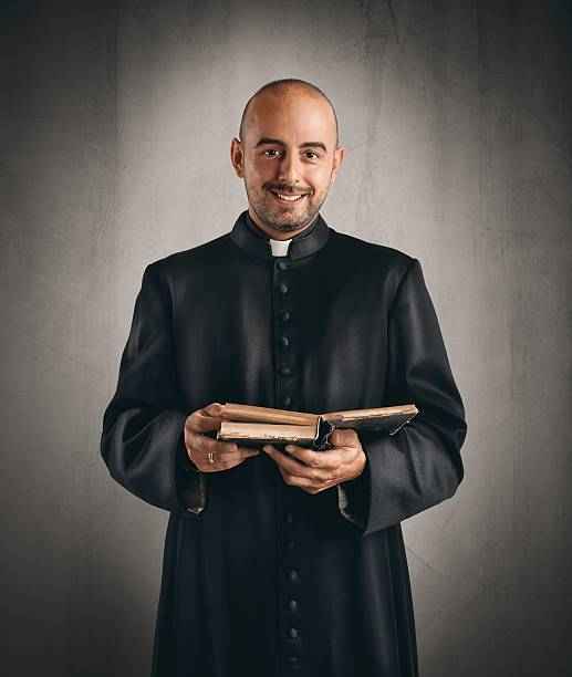 Priest Portrait of  a happy priest that reads a bible clergy stock pictures, royalty-free photos & images