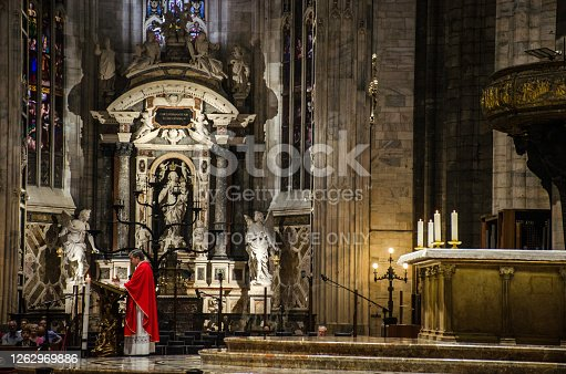 Milan/Italy-July 09, 2016: Priest preaching at the altar of Milan Cathedral, one of the biggest gothic cathedrals and famous tourist attraction in Lombardy, Italy
