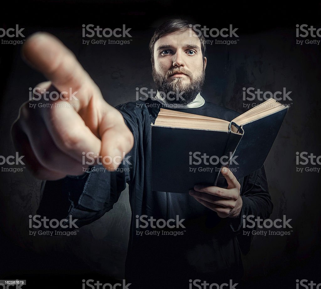 Priest preaching from Bible and pointing finger stock photo