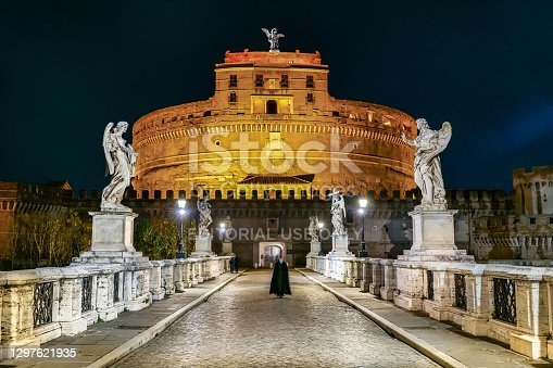 Rome, Italy, January 08 -- A Catholic priest protected by a medical mask due to the Covid crisis crosses the solitary Ponte Sant'Angelo in the heart of Rome at night. Image in high definition format.