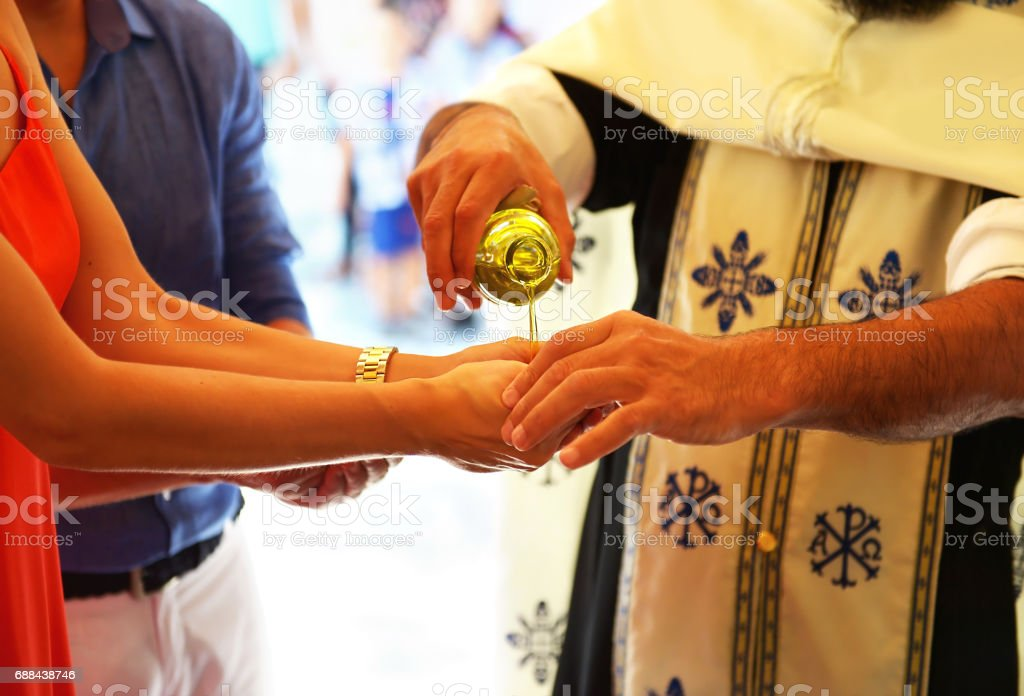 priest puts baptism oil on the hand of godmother Greece stock photo