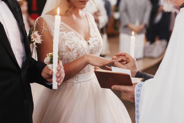 padre colocando em ouro anel de casamento no dedo da noiva. matrimônio de casamento na igreja. trocando alianças - catolicismo - fotografias e filmes do acervo
